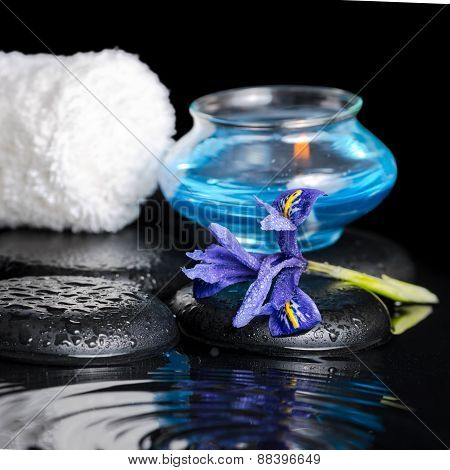 Beautiful Spa Concept Of Iris Flower, Blue Candle, White Towel And Black Zen Stones On Ripple Reflec