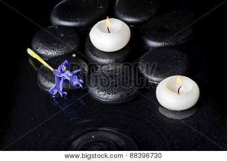 Beautiful Spa Concept Top Down Of Iris Flower, Candles And Black Zen Stones On Ripple Reflection Wat
