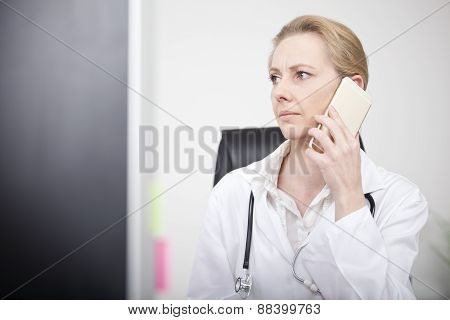 Woman Doctor Calling On Mobile And Looking To Left