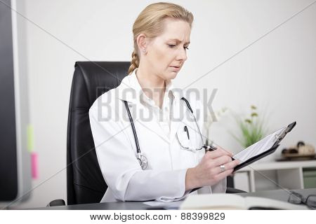 Serious Female Doctor Making Medical Findings