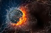 picture of infernos  - Speedometer on fire and water with lightening around on black background - JPG