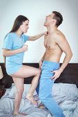 stock photo of genital  - Photo of young angry woman in panties kicking with leg handsome half naked man in groin or genitals with painful face expression - JPG