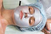 picture of face mask  - Beautician working on a face model in a spa salon - JPG