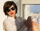 picture of daydreaming  - Girl with sunglasses daydreaming sitting by the window - JPG