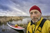 pic of early spring  - senior paddler in life jacket with his paddleboard and lake in background - JPG
