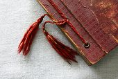 stock photo of tassels  - Old worn out red photo album corner with two tassels on flax canvas - JPG