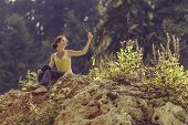image of climber plant  - Happy young lady enjoying the nature while resting in the sunlight on top of a rock during a hike - JPG