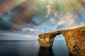 picture of gozo  - Azure Window natural arch famous landmark and popular tourist spot on Gozo island Malta Mediterranean with clouds blue skies and dramatic sunrays - JPG