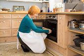 stock photo of oven  - Blond Middle Age Woman With Apron Putting a Cake for Snacks in an Oven at the Home Kitchen - JPG