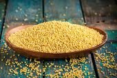 picture of millet  - organic millet seeds in a wooden bowl on rustic table - JPG