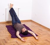 foto of legs apart  - Man relaxing on the floor with his legs up on radiator on wall - JPG