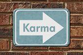 stock photo of karma  - Karma Sign A blue sign with the words Karma on a brick wall - JPG