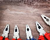 stock photo of pliers  - copyspace image set of handtools pliers on vintage wooden board construction concept - JPG
