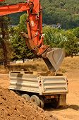image of dump_truck  - Exchavator track hoe loads a dump truck with top soil and loose dirt at a new commercial construction development project - JPG