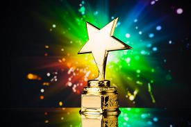 picture of star shape  - gold star trophy against rainbow sparks background - JPG
