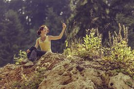 picture of nature conservation  - Happy young lady enjoying the nature while resting in the sunlight on top of a rock during a hike - JPG