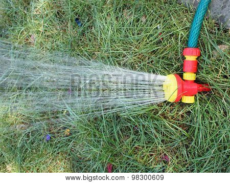 Hose With A Spray Watering The Lawn Closeup
