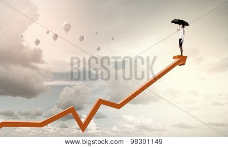 Young businesswoman with black umbrella standing on graph top