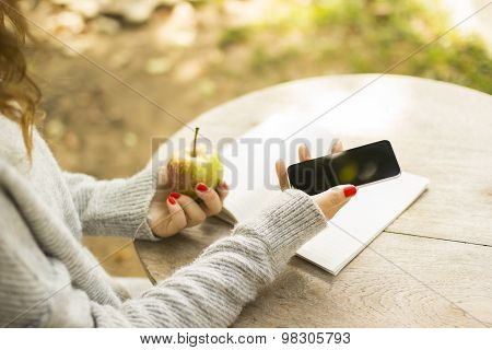Girl With Cell Phone, Diary And Green Apple