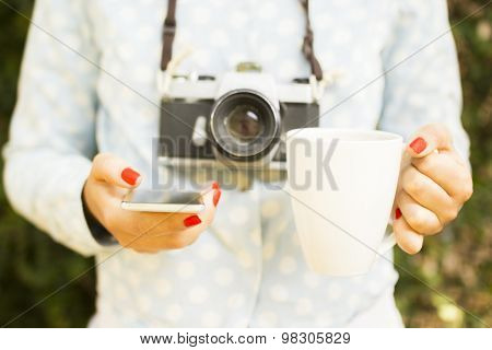 Girl With Cell Phone, Cup Of Coffee And Old Camera