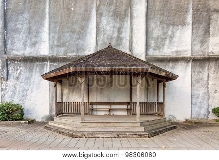 wooden gazebo with a bench against building wall in a street park, copy space
