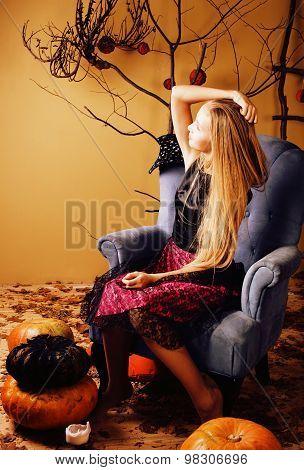 blond cute girl in halloween interior with pumpkin