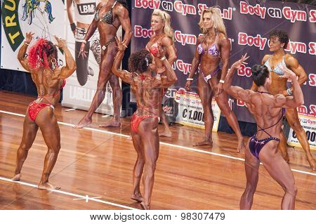 Female Bodybuilders In Back Double Biceps Pose On Stage