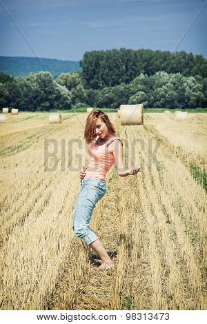Redheaded Young Woman Imitates Guitar Play At The Field