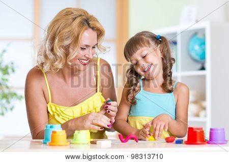 Kids playing with colorful clay molding different shapes