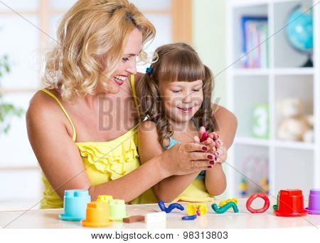 child with mom making by hands