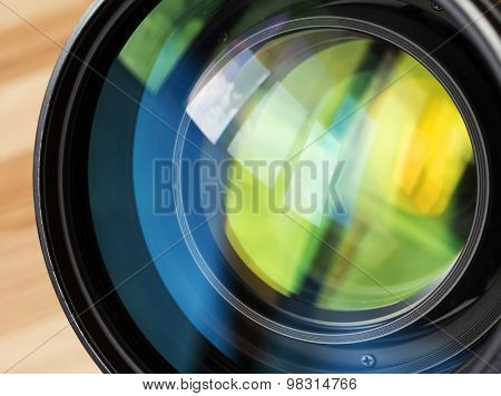 Macro shot of front element of a lens with beautiful color lights reflections