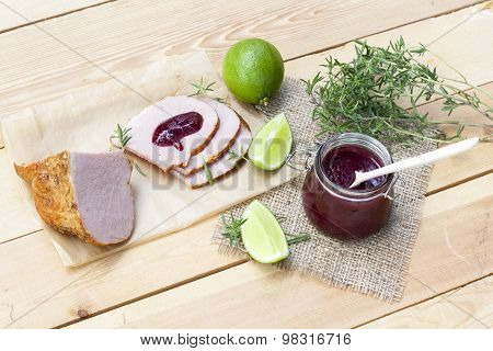 Home made organic cherry jam confiture, smoked meat and lime on a wooden table