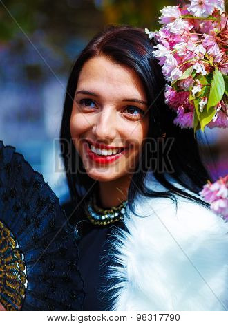 Beautiful Woman with flowers, glamour white fur and black fan in hand, posing next to blooming magic