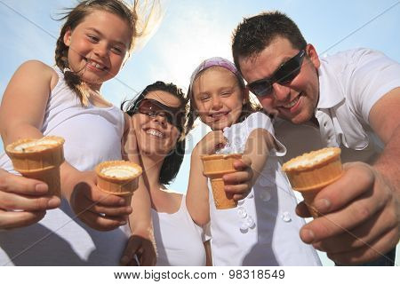 family eating ici-cream in front of ocean