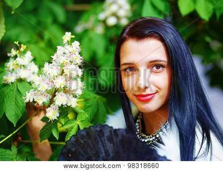 Beautiful Girl with flowers, glamour white fur, posing next to blooming magical spring  flowers. Flo