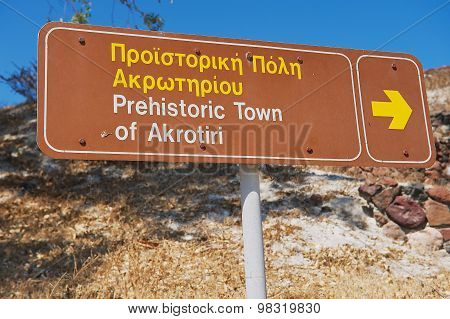 Exterior of the sign pointing to the Akrotiri archaeological site in Akrotiri, Greece.