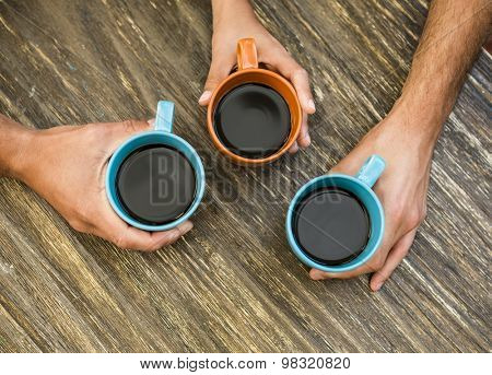 Hands holding cups of coffee over a table