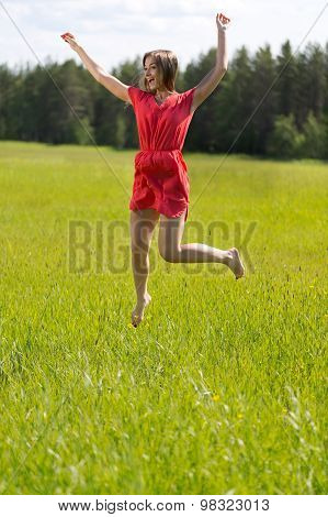 Young Girl In A Red Dress Jumping In A Field