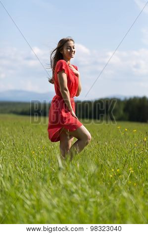 Young Girl In A Red Dress In A Field.