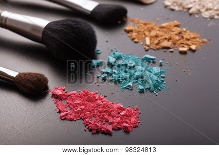 Makeup brushes on background with colorful powder.