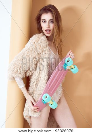 fashion sexy model in fur coat and lingerie promote longboard in studio