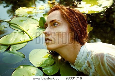 Tender Young Woman Swimming In The Pond Among Water Lilies