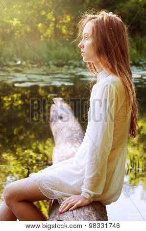 Redhead Woman Sitting On A Tree Bark Near River