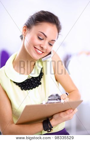Pretty fashion designer working in office using mobile phone .