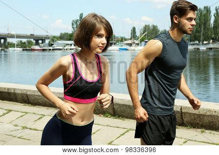 Young people jogging near river