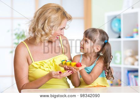 kid and mother playing at table at home