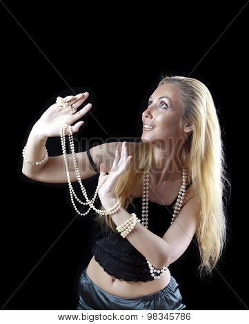 The beautiful blonde woman with long hair with a pearl beads looks upward with a smile and shielded