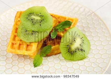 Sweet homemade waffles and fresh kiwi fruit on plate, close-up