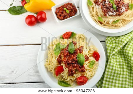 Spaghetti Bolognese on white plate, on color wooden background