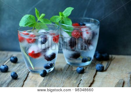 Glasses of cold refreshing summer drink with berries and ice cubes on table close up